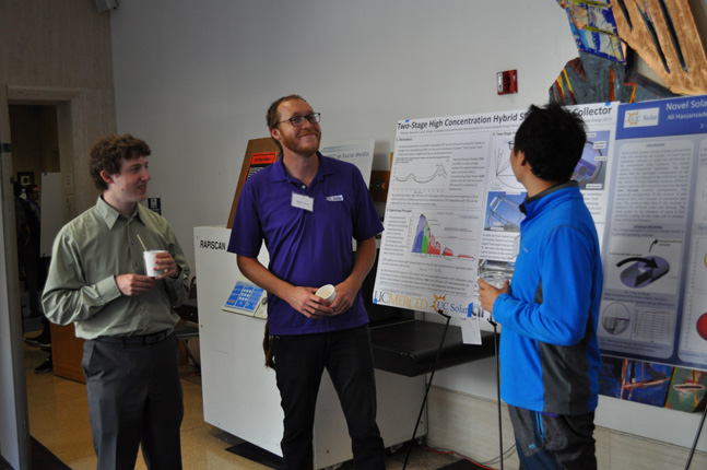 UC Merced doctoral candidate Bennett Widyolar (center) is all smiles standing next his winning poster, which received the largest share of the audience votes.