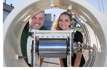Graduate student Jonathan Ferry and undergraduate mechanical engineering major Jordyn Brinkley show off the solar-powered drum dryer.